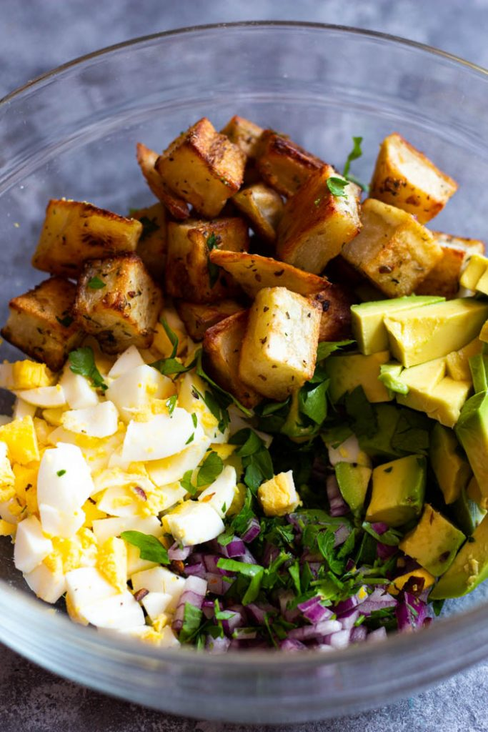 Once the potatoes are roasted, mix them with eggs, avocados, potatoes, red onion and vinegar.