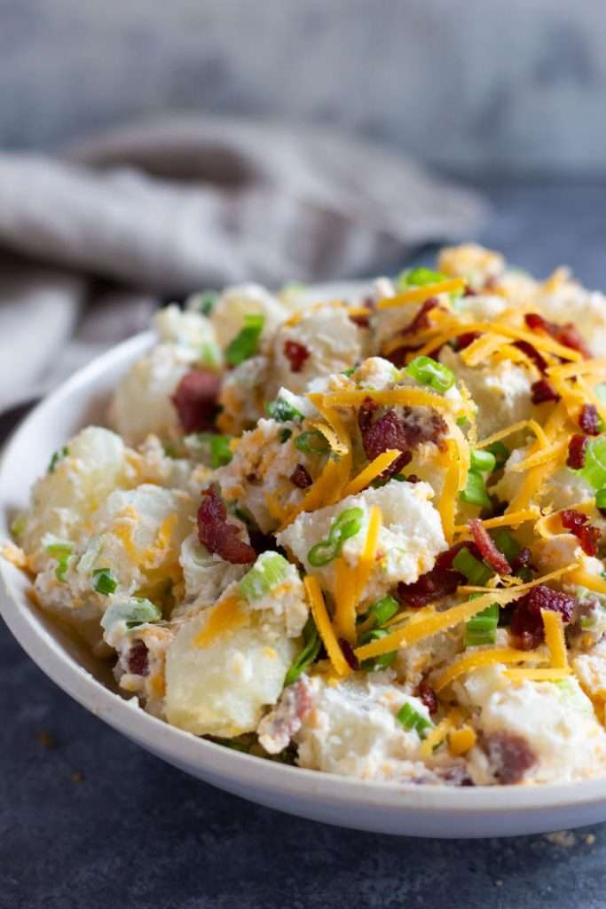 Loaded baked potato salad in a bowl topped with extra bacon and cheese.